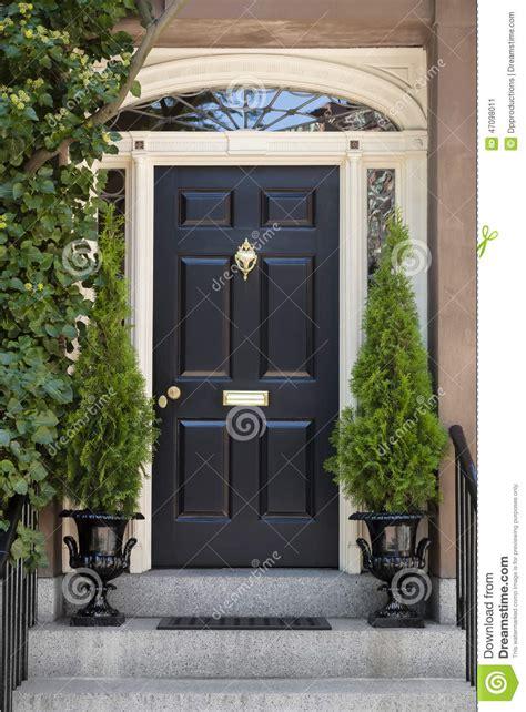 black front door  white door frame  greenery stock