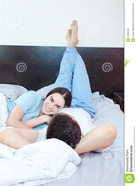 good morning kiss in bedroom smiling couple in love lying on bed in bedroom stock photo image 51885248