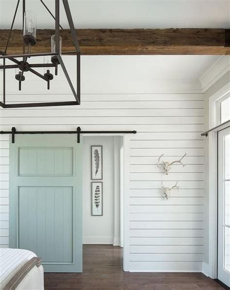 Cottage Bedroom Boasts A White Shiplap Wall Fitted With A Blue Barn Door