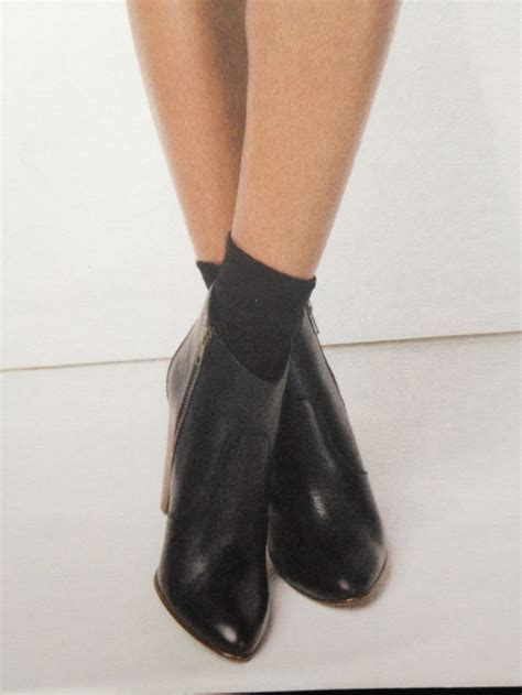 ankle boots with socks one foot ahead of the other
