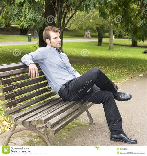 sitting in a park bench man sitting on a bench in the park stock image image of