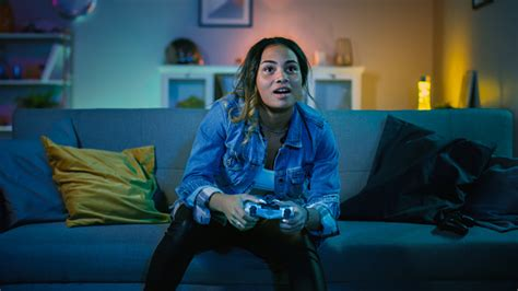beautiful excited young black gamer girl sitting