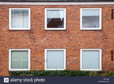 red brick wall with square windows closed with white