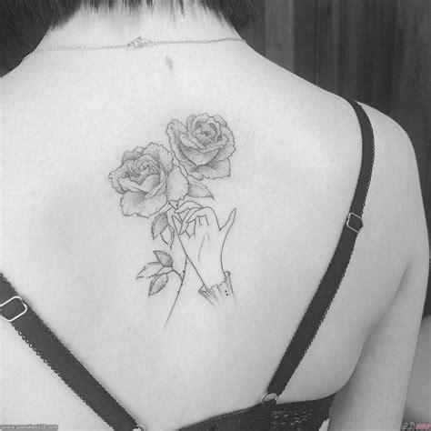 女子背上简洁精致的手拿玫瑰花纹身图案
