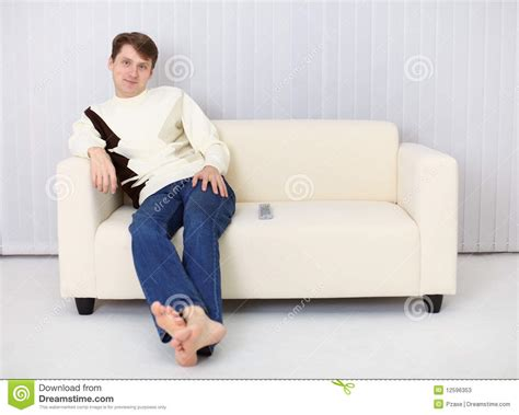 sitting in sofa young man sits on sofa and has rest stock photos image