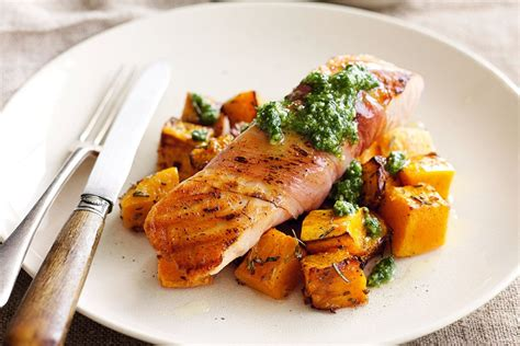 fish cuisine salmon wrapped in prosciutto with pesto and roast pumpkin