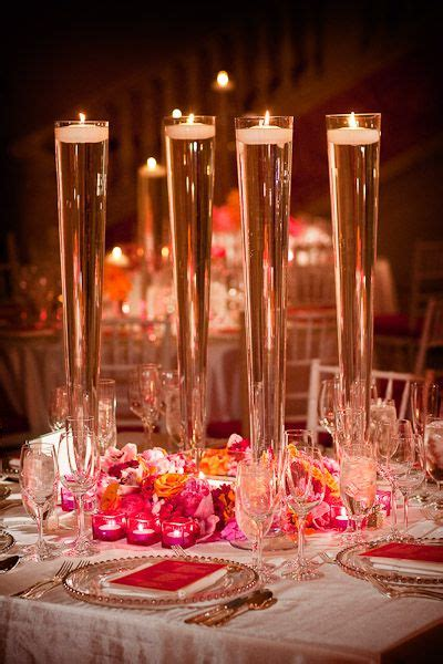 wedding centerpieces with candles and water footed vases with water and floating candles