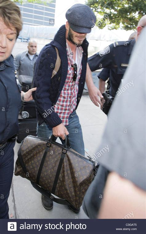 Louis Vuitton David Beckham With His Louis Vuitton Sac Squash And Pegase Luggage by David Beckham Carrying His Louis Vuitton Travel Bag Gets