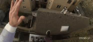 Guy jumps off a building slides down a roof and lands on stairs for