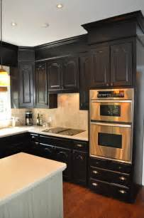 Extend the drama of your black kitchen cabinets by painting the