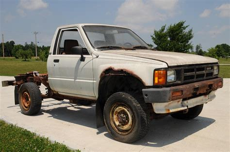 rusty pickup breaking a rusty toyota pickup truck frame with a hammer