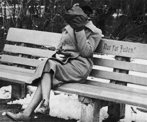 bench marked a jewish woman who is concealing her face sits on a park