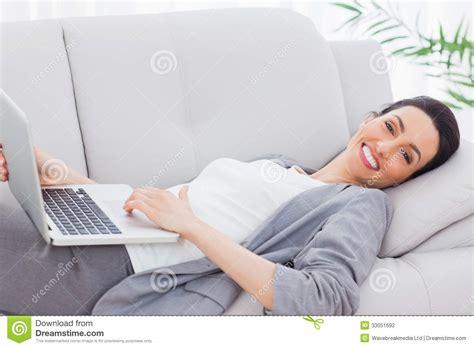 lying on sofa happy businesswoman lying on sofa using laptop stock