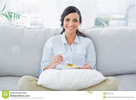 woman eats couch pretty woman sitting on the couch crossing legs eating