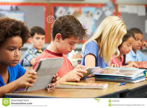 Pupils In Class Using Digital Tablet Royalty Free Stock Student Working At Desk