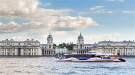 thames clipper and royal observatory stand alongside the meridian line in greenwich london