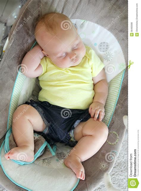 using a swing for baby to sleep chubby newborn baby girl sleeping in infant swing stock