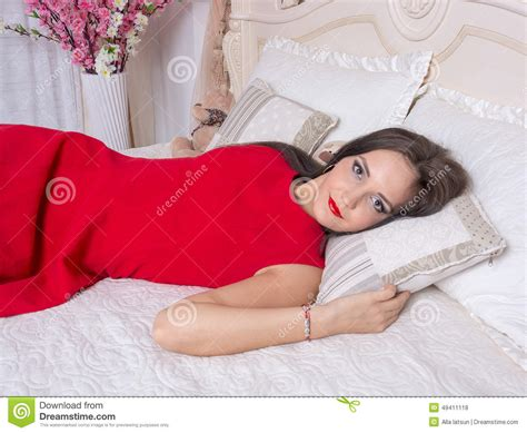 bed dress young woman in a red dress on the bed stock photo image
