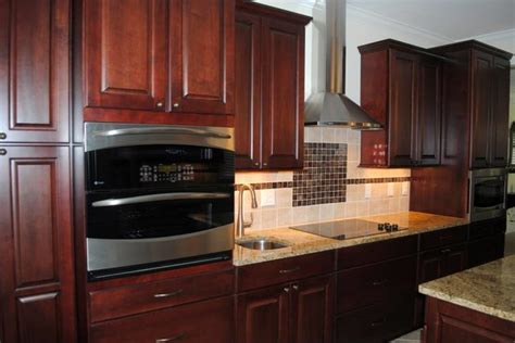 maple cabinets in cranberry with black stain normandy candlelight backsplash