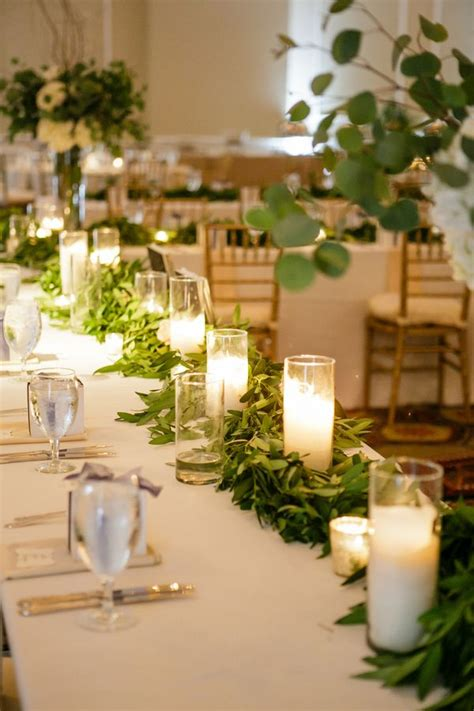 Wedding Aisle With Tables by Greenery And Candle Table Runner Greenery Photography