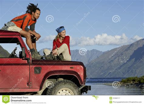 jeep couple couple sitting on jeep by mountain lake stock image