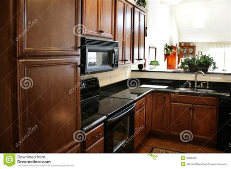 kitchen wood cabinets black and stainless stove royalty