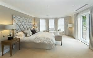 Large windows wrap this white toned bedroom spiked with a massive