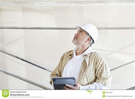 male architect with digital tablet studying plans in mature male architect making a note in digital tablet