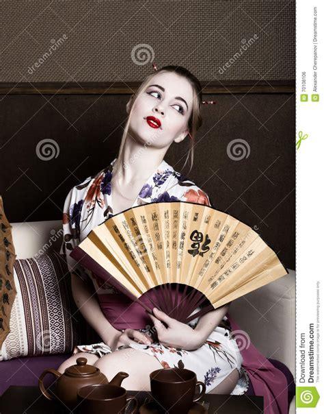 Eyeliner Kimono beautiful dressed as a geisha she holds a