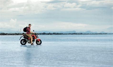 Motorrad Spiele Gratis Downloaden by Biker Posiert Mit Seinem Motorrad Auf Dem Meerwasser