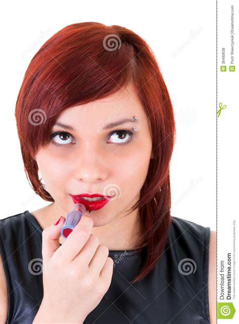portrait of teenage girl putting lipstick on while looking at her teenage girl applying lipstick royalty free stock photos