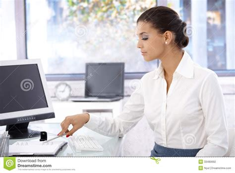 pretty sitting at desk working stock photography