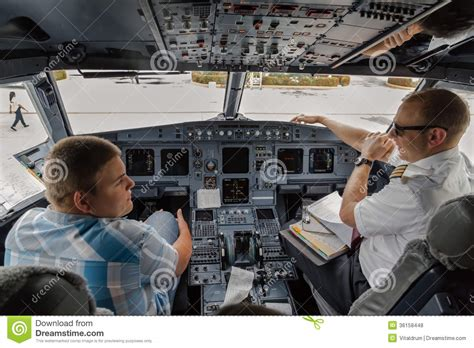 a day in the of an airline pilot books student and pilot talking in the plane cockpit editorial