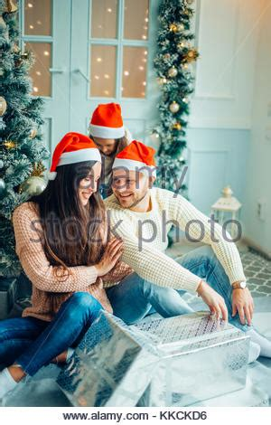 house interiors and gifts family exchanging christmas presents in front of their tree on stock photo royalty