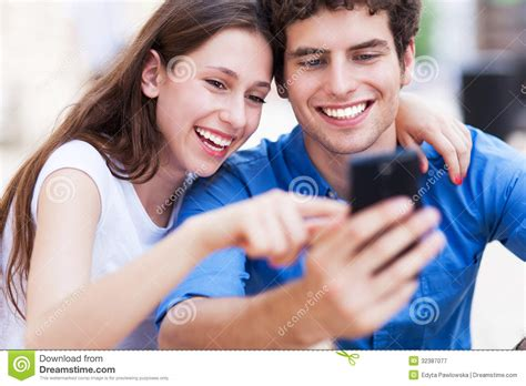 For Couples On Phone Looking At Mobile Phone Stock Image Image