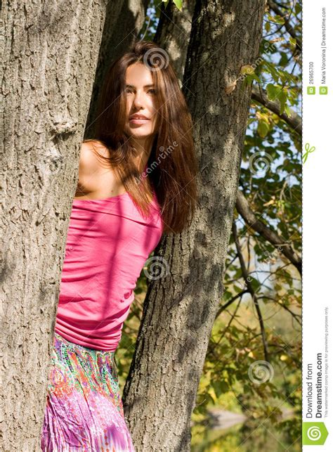 beautiful woman by the tree looking up stock photo image beautiful girl standing near tree stock photo image