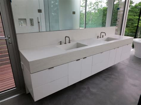 white concrete bathroom vanity sink with faucets