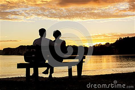 bench couple watch couple watching a beautiful sunset together stock photo