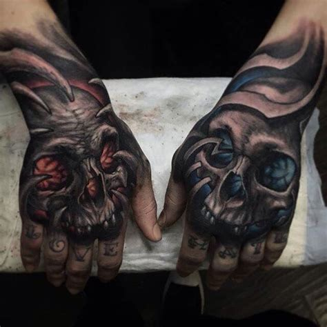 evil tattoo on hand skull design on left hand w blue proyect tattoo