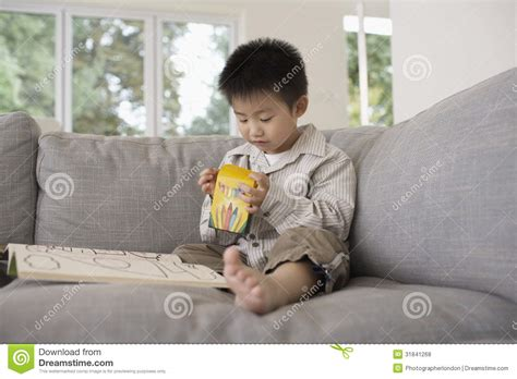 boy on couch boy with coloring book sitting on sofa stock photo image