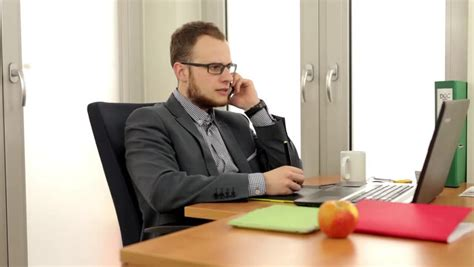 Person Sitting At A Desk by Worried Businessman Sitting At Office Desk With Tablet And Paperwork Stock Footage 2010419