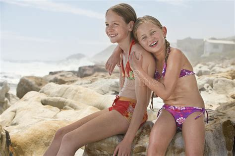 girls heliosnatura hd naturism freedom 2016 family happy little girl sitting with sister on rocks stock image