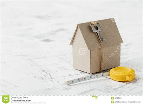 design concepts expert contractors model cardboard house with key and tape measure on