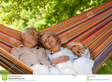 Couple Sleeping And Hugging senior couple relaxing in hammock stock photography