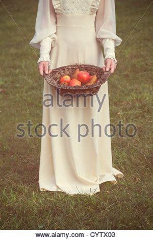 woman   white edwardian dress  holding  basket