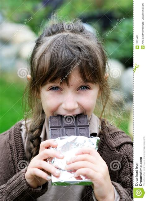 small tiny little cute girl eating chocolate stock photo image