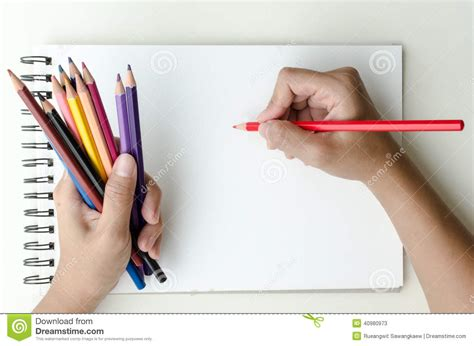 sketchbook and pencils holding colored pencils and sketching stock image
