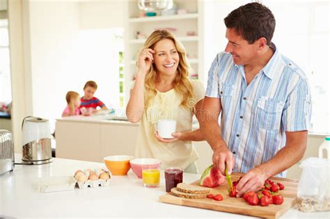 The Oz Family Kitchen by Parents Preparing Family Breakfast In Kitchen Stock Images