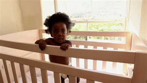 Cute Baby Girl Standing In Her Crib Looking At Camera At Baby Standing In Crib