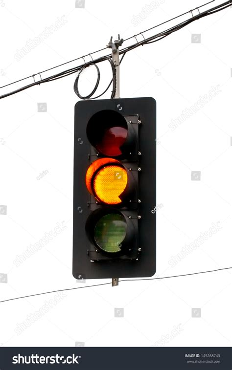 yellow traffic light hanging from wires overhead up